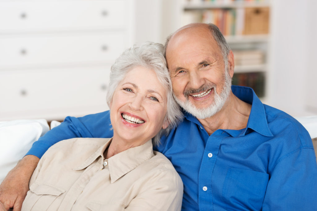 Smiling older couple who got dentures in just one day at the Anchorage, AK office of Dentures Alaska.